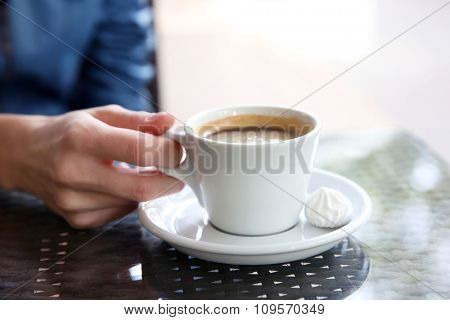 Cup of coffee with hands and zephyr on table in cafe background
