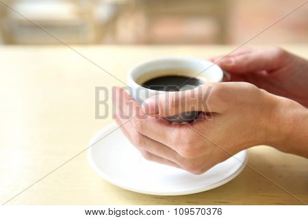 Cup of coffee with hands on table in cafe background