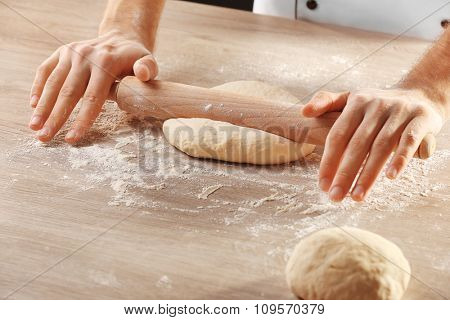 Hands rolling dough for pizza on the wooden table, close-up