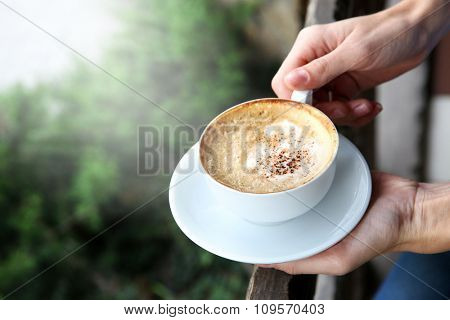 Cup of tasty cappuccino with hands on street background