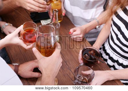 View on friends having alcoholic drinks in the bar, close-up