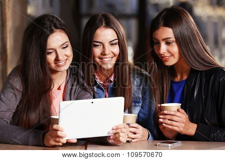 Best friends with tablet together sitting at cafes terrace