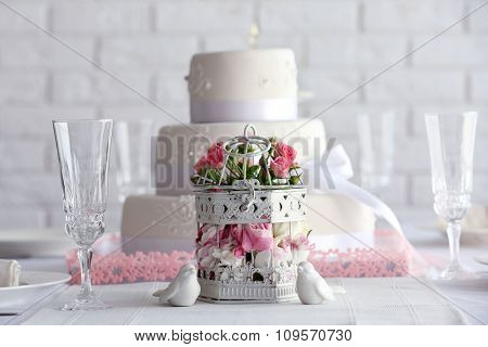 Wedding layered cake in decorated restaurant on white wall background