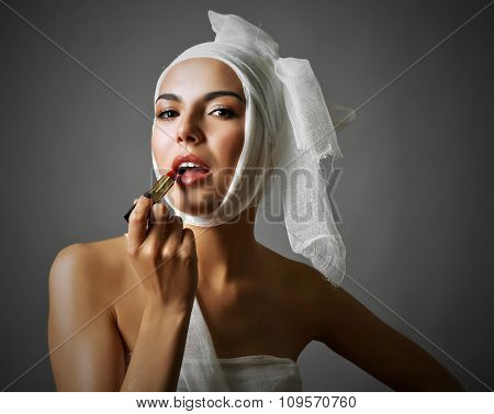 Young emotional woman with a gauze bandage on her head and chest, holding lipstick, on grey background