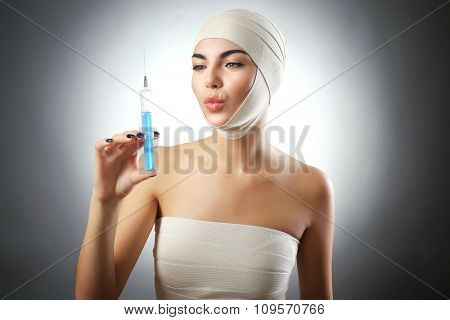 Young emotional woman with an elastic bandage on her head and chest, on grey background