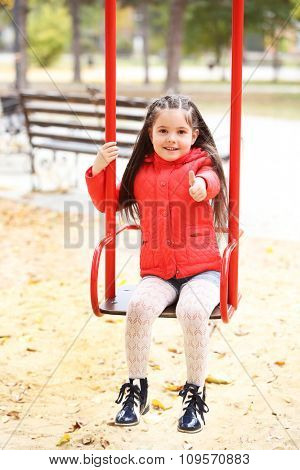 Little girl on swing in city park