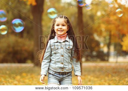 Cute girl playing with soap bubbles in park