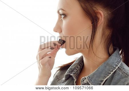 Woman eating blackberry at home