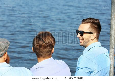 Young men relaxing on the riverside