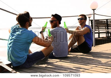 Young men sitting on the dock and talking with each other