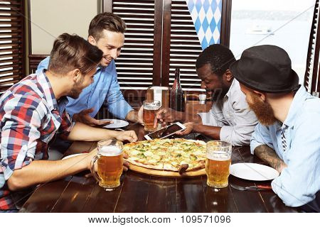 Young men drinking beer and talking in cafe