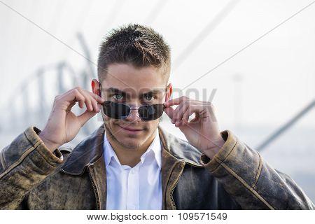 Handsome trendy man standing on a sidewalk