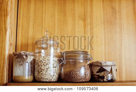 real comfort wooden kitchen with breakfast ingredients close up in glass, honey, oatmeal, milk, mues