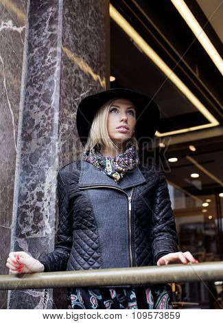 young pretty blond woman in stylish hat, street fashion european cold weather
