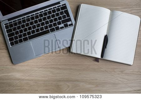 Laptop and Notepad with pen on a wooden Desk.