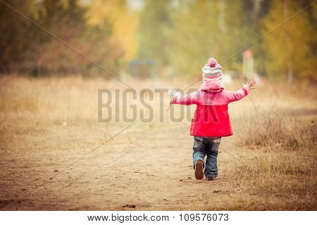 Little girl walking with windmill on autumn landscape. back view