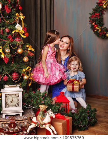 Daughter Kissing Mother Near Christmas Tree.
