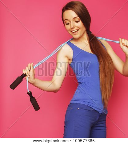 young happy slim girl with skipping rope on pink background smiling sweety