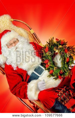 Good old Santa Claus sitting in a rocking chair and holding Christmas wreath. Red background. Christmas.