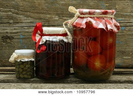 Jar With Preserves. Homemade Strawberry Jam, Pickled Tomatoes And Capers On Wooden Background