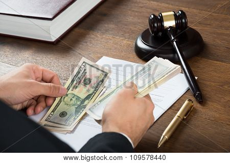 Corrupt Judge Counting Money At Desk