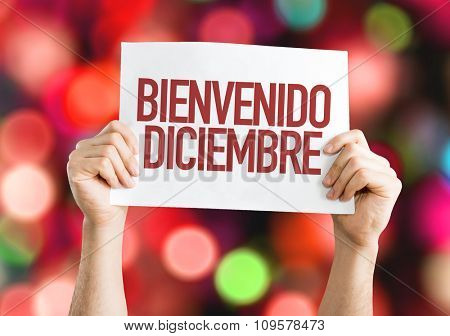 Welcome December (in Spanish) placard with red bokeh background