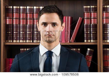Portrait Of Confident Lawyer Against Bookshelf