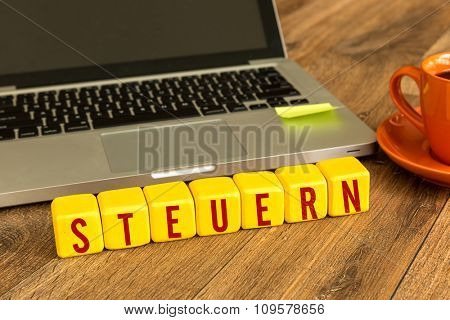Tax (in German) written on a wooden cube in a office desk