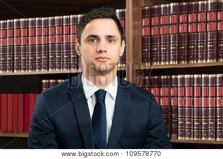 Confident Lawyer Standing Arms Crossed Against Bookshelf