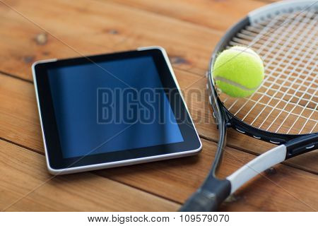 sport, fitness, technology, game and objects concept - close up of tennis racket with ball and tablet pc computer on wooden floor