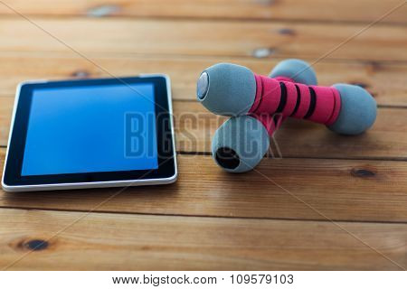 sport, fitness, technology and objects concept - close up of dumbbells and tablet pc computer on wooden floor
