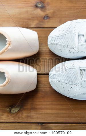 sport, ballet, fitness, footwear and objects concept - close up of sneakers and pointe shoes on wooden floor