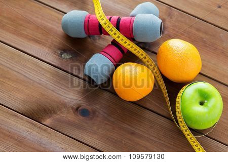 sport, fitness, diet and objects concept - close up of dumbbell and green apple with oranges wrapped by measuring tape on wooden table