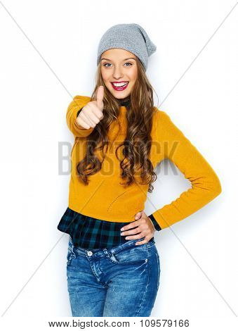 people, style and fashion concept - happy young woman or teen girl in casual clothes and hipster hat showing thumbs up