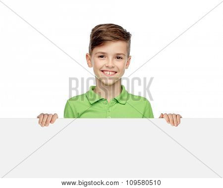 childhood, advertisement and people concept - happy smiling boy in green polo t-shirt holding white blank board