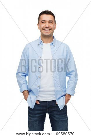 happiness and people concept - smiling man with hands in pockets
