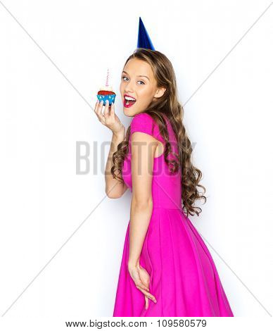 people, holidays and celebration concept - happy young woman or teen girl in pink dress and party cap with birthday cupcake