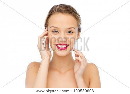 beauty, people and health concept - smiling young woman face with pink lipstick on lips and shoulders