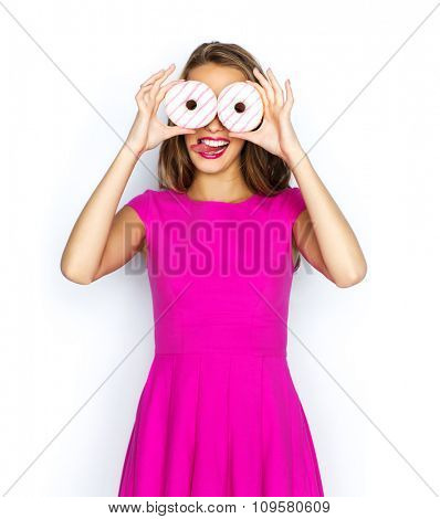 people, holidays, junk food and fast food concept - happy young woman or teen girl in pink dress having fun, looking through donuts and showing tongue