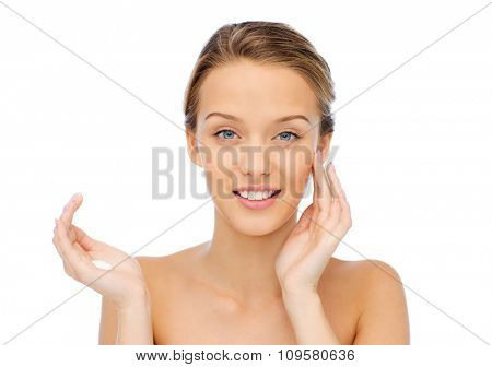 beauty, people, cosmetics, skincare and health concept - happy smiling young woman applying cream to her face