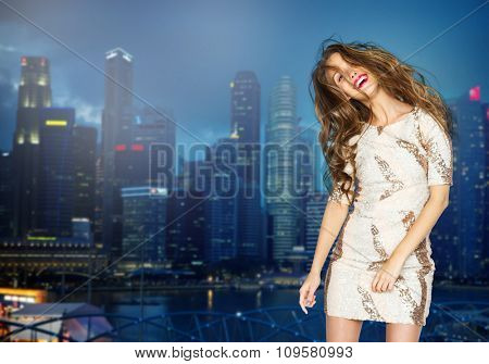 people, style, holidays and fashion concept - happy young woman or teen girl in fancy dress with sequins and long wavy hair dancing at party over night singapore city background