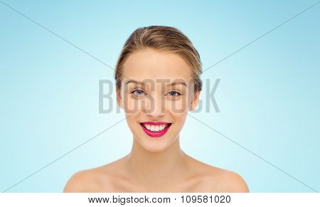 beauty, people and health concept - smiling young woman face with pink lipstick on lips and shoulders over blue background