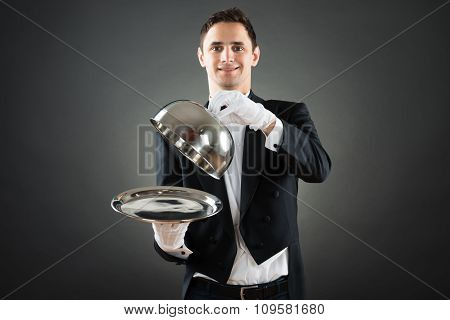 Portrait Of Waiter Holding Cloche Over Empty Tray