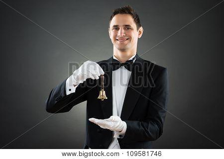 Portrait Of Happy Waiter Holding Ring Bell