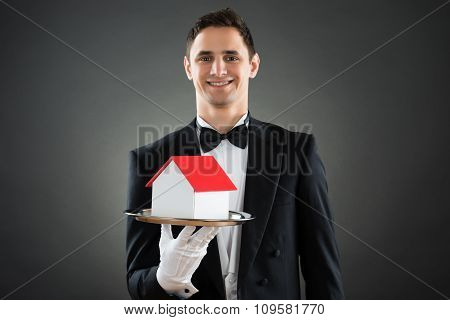 Happy Waiter Holding House Model In Tray