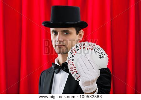 Magician Holding Fanned Out Cards Against Red Curtain