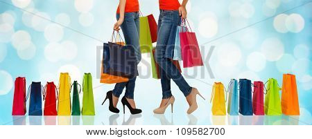 people, sale and consumerism concept - close up of women with shopping bags over blue holidays lights background