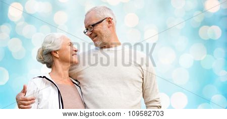 family, old age, love and people concept - happy senior couple over blue holidays lights background