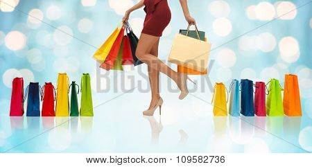 people, sale and consumerism concept - close up of woman in red short skirt and high heeled shoes with shopping bags over blue holidays lights background