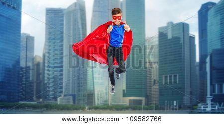 happiness, freedom, childhood, movement and people concept - boy in red super hero cape and mask flying in air and showing thumbs up